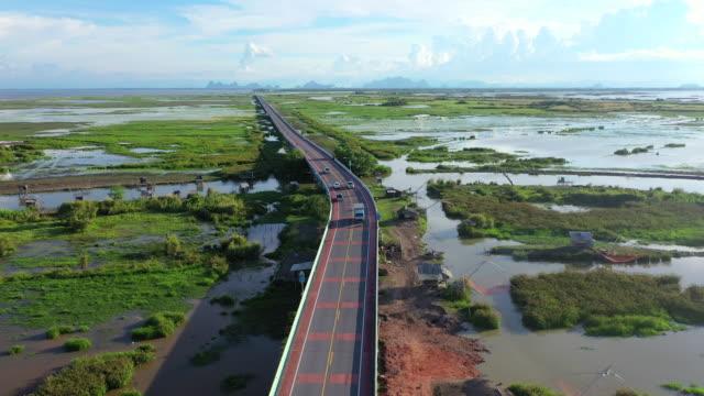 4k空中ドローン映画は、パッタルン、タイの自然湖を横切る高速道路橋の上を飛びます - eco tourism点の映像素材/bロール