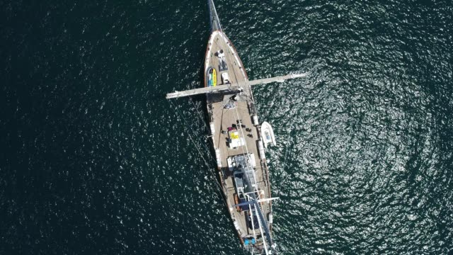 4k aerial drone shot of tall ship in black ocean - sailing team stock videos & royalty-free footage