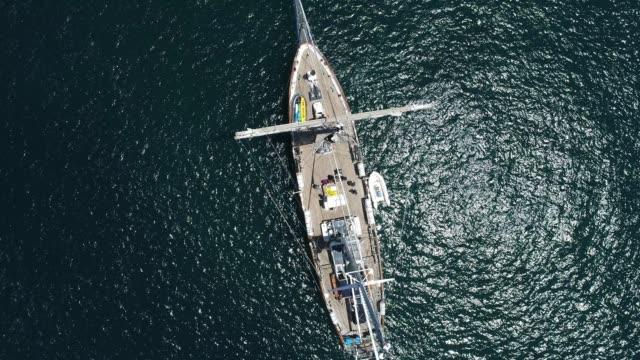 4k aerial drone shot of tall ship in black ocean - segelmannschaft stock-videos und b-roll-filmmaterial