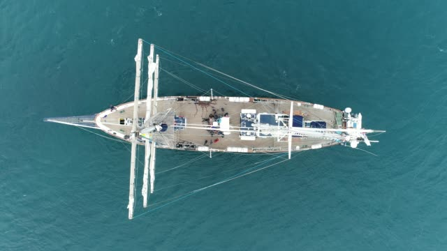 4k aerial drone shot of tall ship in ocean - stability stock videos & royalty-free footage