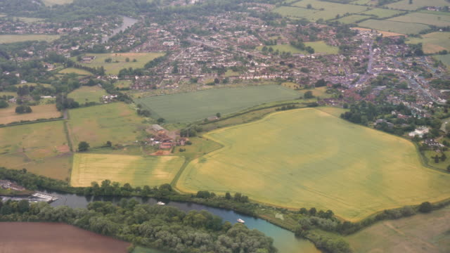 4k aerial drone style footage of old windsor and rural english countryside as plane comes into land at london heathrow airport lhr - エセックス州点の映像素材/bロール