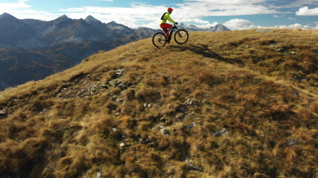 4k aerial drone view man biking up ridge - mountainbiking stock-videos und b-roll-filmmaterial