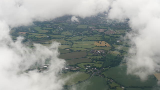 4k aerial footage of rural english countryside showing green fields, farms and crops on a summers day. - landing touching down stock videos & royalty-free footage