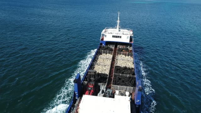 4k aerial of ferry at sea, carrying sheep and cattle