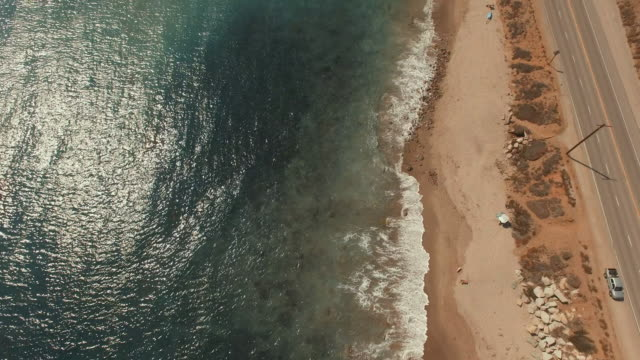 4k aerial pan up over a beach in malibu, california - malibu stock videos & royalty-free footage