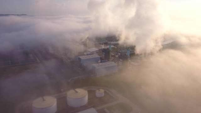 4k aerial shot of combine cycle power plant and cooling tower in mist at south east asia - smoke stack stock videos & royalty-free footage