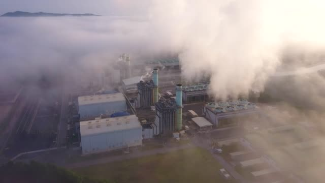 4k Aerial shot of combine cycle power plant and cooling tower in mist at south east asia