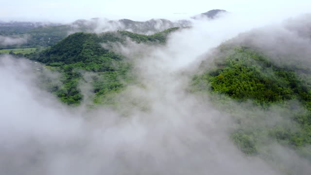 4k aerial shot of fog rolls across flowing over mountains at ratchaburi province, thailand. - tracking shot stock videos & royalty-free footage
