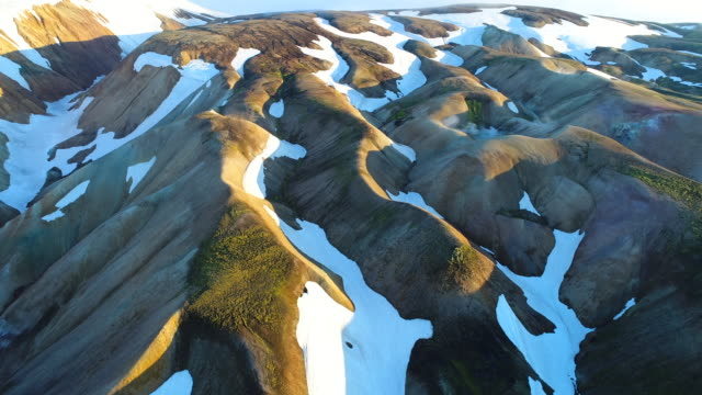 4k aerial shot of valley national park landmannalaugar. on the gentle slopes of the mountains are snow fields and glaciers. magnificent iceland in the summer - glacier stock videos & royalty-free footage