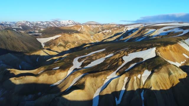 4 k aérienne un coup de la vallée du Parc National de Landmannalaugar. Sur les pentes des montagnes sont les champs de neige et les glaciers. Magnifique Islande en été
