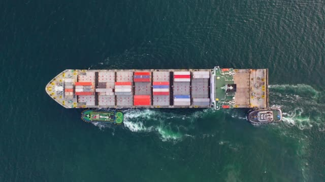 4k aerial shot track of container ship in ocean of south east asia - on top of stock videos & royalty-free footage