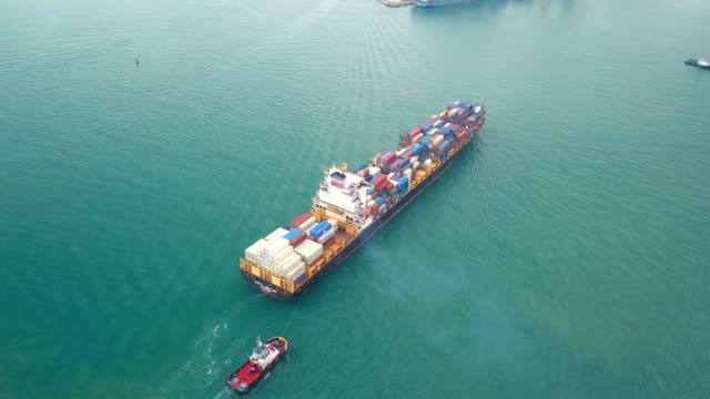 4k aerial shot track of container ship in ocean - on top of stock videos & royalty-free footage