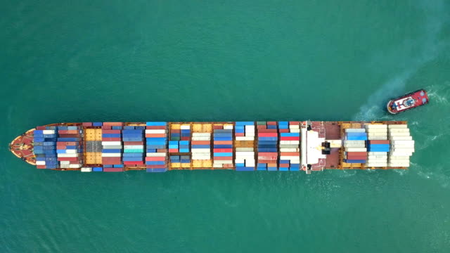 4k aerial shot track of container ship in ocean - overhead view stock videos & royalty-free footage