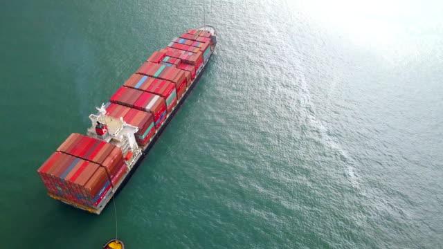 4k aerial shot track of container ship in ocean - cargo ship stock videos & royalty-free footage