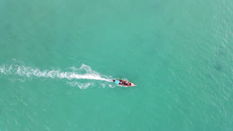 4k aerial top view tracking follow of long tail boat in shallow water sea ocean - speed boat stock videos & royalty-free footage
