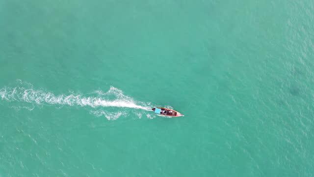 vidéos et rushes de suivi de vue aérienne de 4k suivant du bateau de longue queue dans l'océan de mer peu profond d'eau - vue en plongée verticale