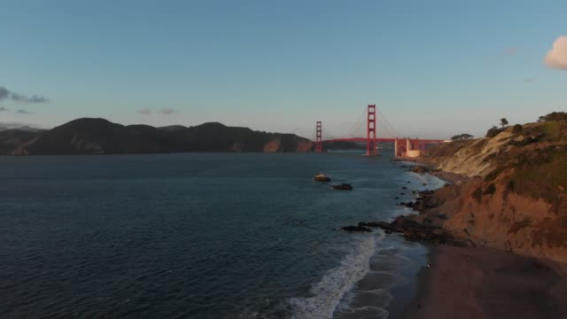 vídeos de stock, filmes e b-roll de vídeo aéreo de 4k-praia do padeiro em san francisco, califórnia vista da ponte de porta dourada no por do sol - golden gate bridge