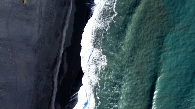4k aerial video of waves splashing over a black beach - dyrholaey stock videos & royalty-free footage