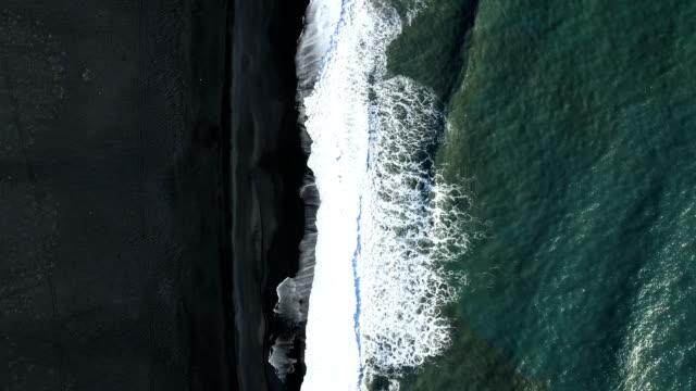 4k aerial video of waves splashing over a black beach