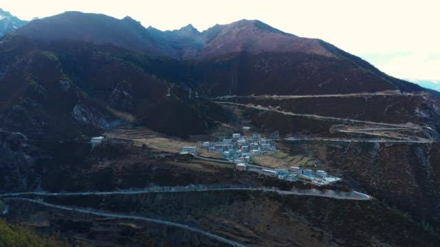 4k aerial view and dolly back of village in valley. - tibetan plateau stock videos & royalty-free footage