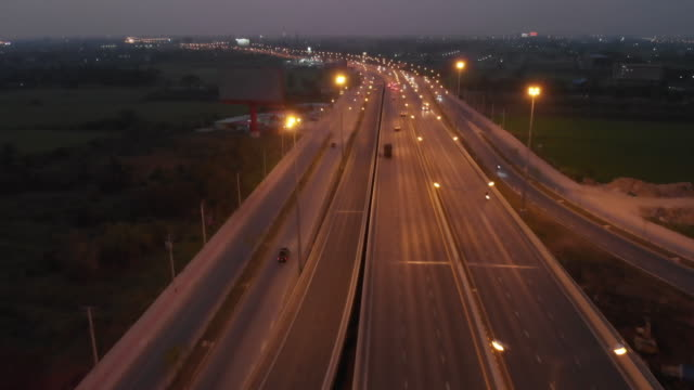 4k aerial view and dolly shot with tilt up of road at night time. - major road stock videos & royalty-free footage