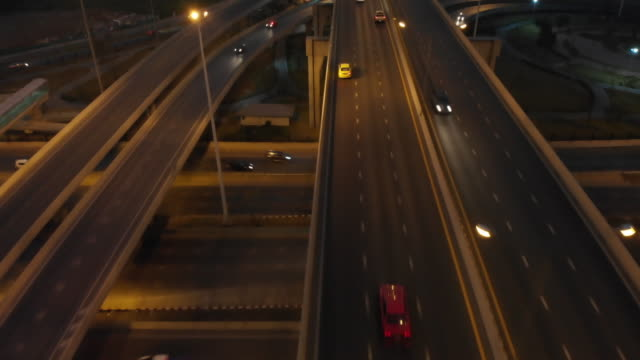 4k aerial view and dolly shot with tilt up of road at night time. - tilt up stock videos & royalty-free footage