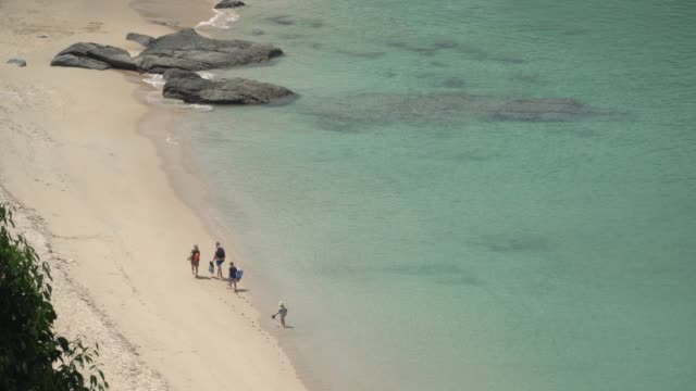 4k aerial view and medium shot of people walking on the beach.