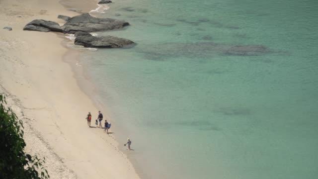 vista aérea de k 4 y medio tiro de personas caminando en la playa.