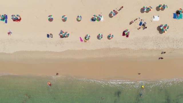 4 vista aérea de k y el zoom de personas en la playa.