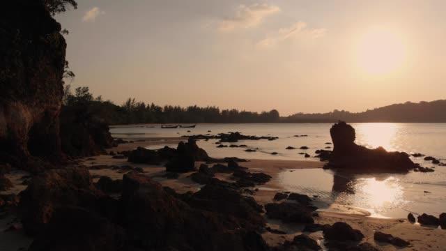 vídeos de stock, filmes e b-roll de dolly de vista aérea 4 k tiro na praia e rochosa em vez do sol. - coluna de calcário marítimo