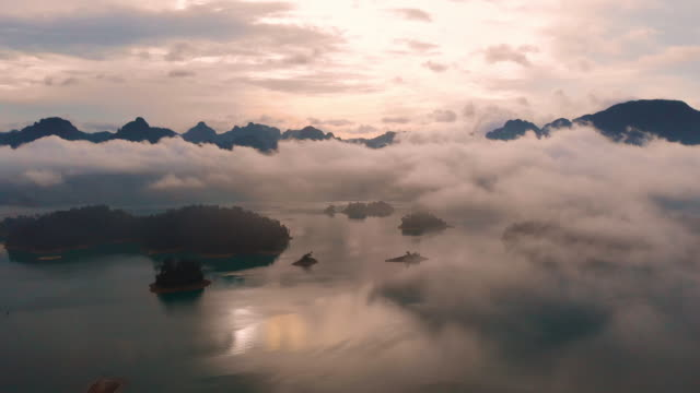 4k aerial view flying above the cloud in morning time at chiaw lan dam in khao sok. - mountain range stock videos & royalty-free footage