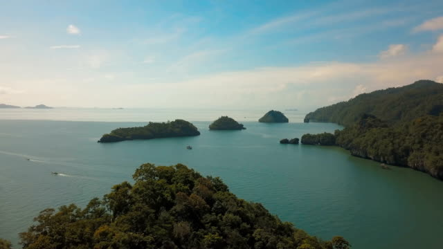 4k aerial view flying over tropical coral reef lagoon towards beautiful green mountains at satun, thailand - island stock videos & royalty-free footage