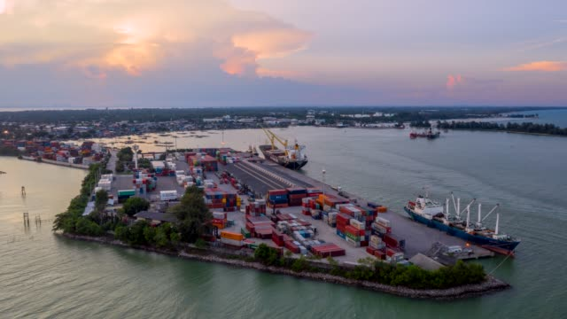 4k aerial view, hyper lapse movie  sunset scene of industrial port with containers ship - unloading stock videos & royalty-free footage