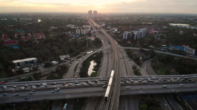 4k aerial view of bts skytrain and city street in sunset time.