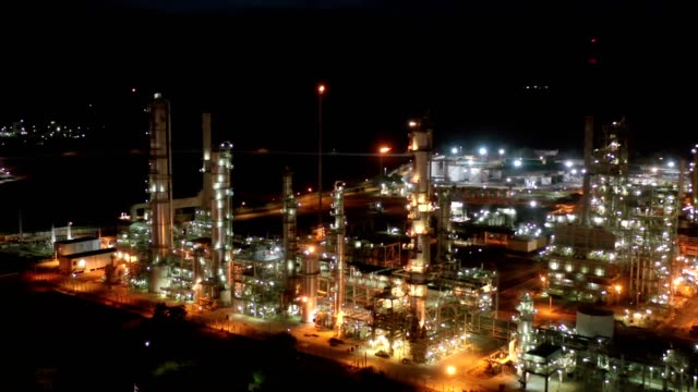 4k Aerial view of large oil refinery facilities and storage tank in Asia at night