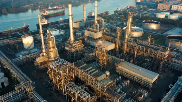 4k aerial view of large oil refinery facilities in asia - smoke stack stock videos & royalty-free footage