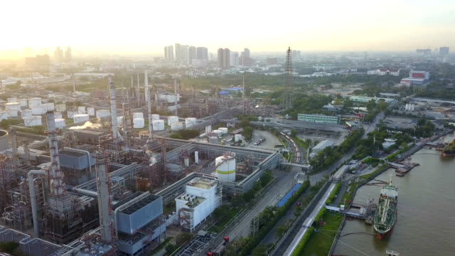 4k aerial view of large oil refinery facilities in sunrise - gas pipe stock videos and b-roll footage