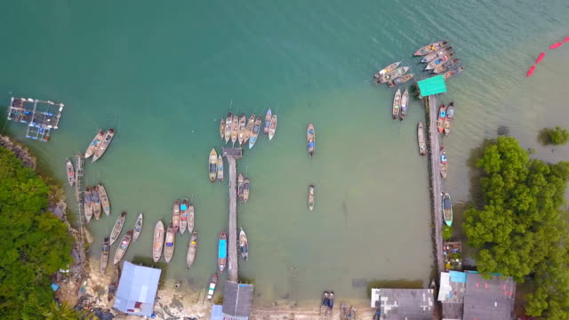 4k aerial view of longtail boat at fishing village in south of Thailand