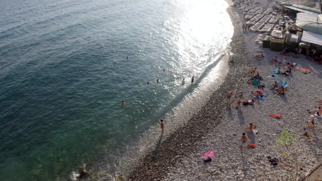 4k aerial view of people relaxing on sun loungers sunbathing and swimming at the beach in nice, france on a bright summer warm day. - french culture stock-videos und b-roll-filmmaterial