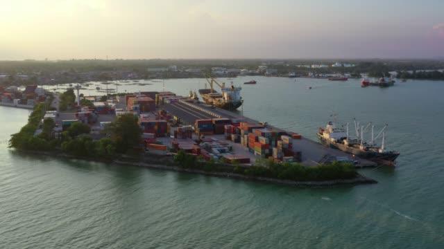 vidéos et rushes de 4 aerial view sunset scène d'industrialo-portuaire k avec conteneurs navire - lieu de culte