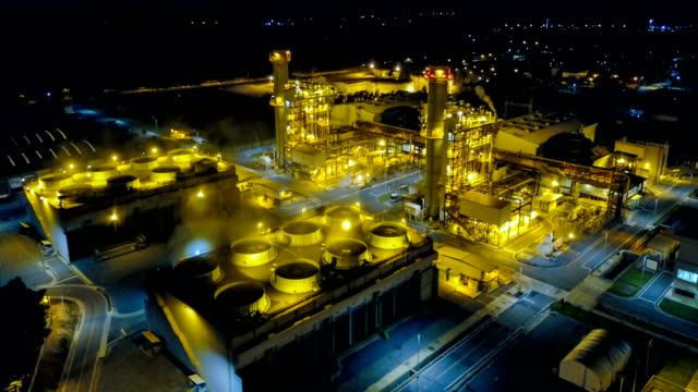 4k aerial view timelapse of combined cycle powerplant or fuel gas powerplant at night - power station stock videos & royalty-free footage