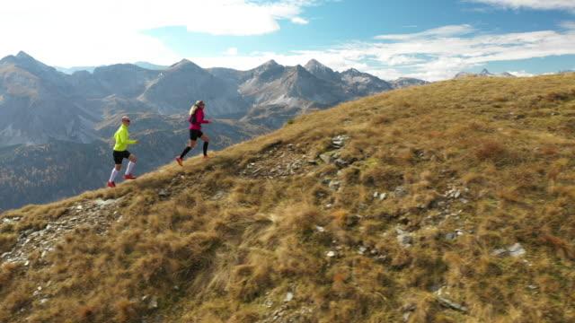 4k aerial view trail runners running on mountain ridge - marathon stock-videos und b-roll-filmmaterial