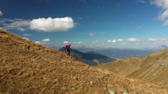4k aerial view woman walking hiking down mountain ridge