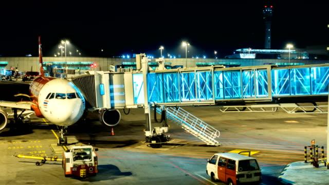 4k flugzeug zeit verfallen am tor mit fluggastbrücke bei nacht - malaysia stock-videos und b-roll-filmmaterial
