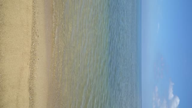 4k and vertical shot of sea beach with blue sky. - vertical stock videos & royalty-free footage