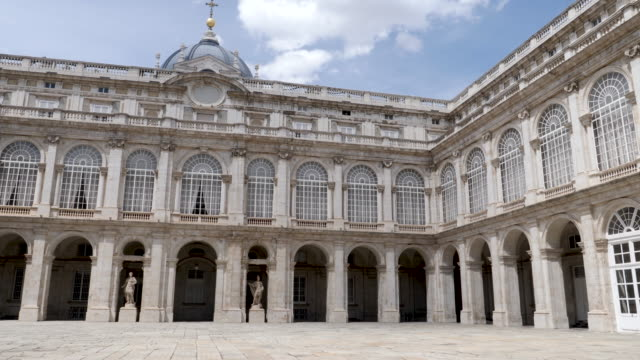 4k architecture shot of the royal palace of madrid inner courtyard plaza. panning shot. no people. bright sunny conditions on summers day. blue skies. - courtyard stock videos & royalty-free footage