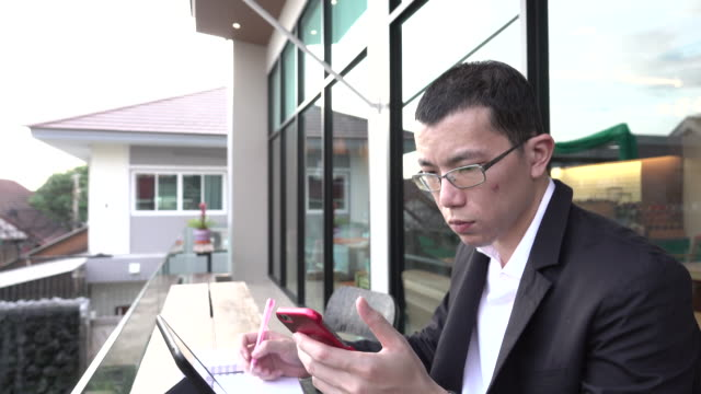 4k: asian businessman playing smart phone with tablet - e learning stock videos and b-roll footage