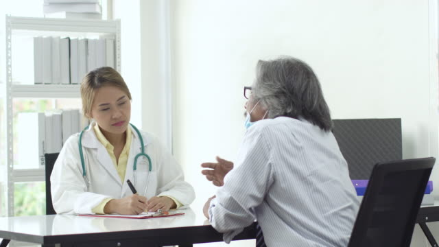 4k: Asian doctor and patient talking about illness in hospital or clinic.