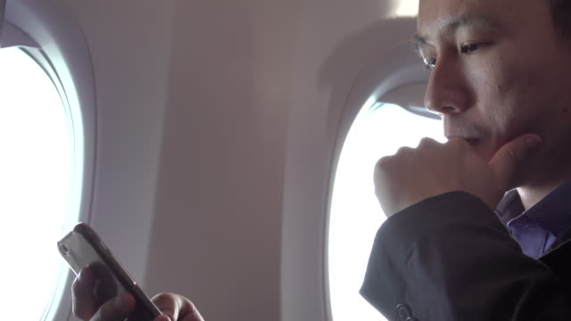 4k: asian man browsing smart phone on the airplane - commercial airplane stock videos & royalty-free footage