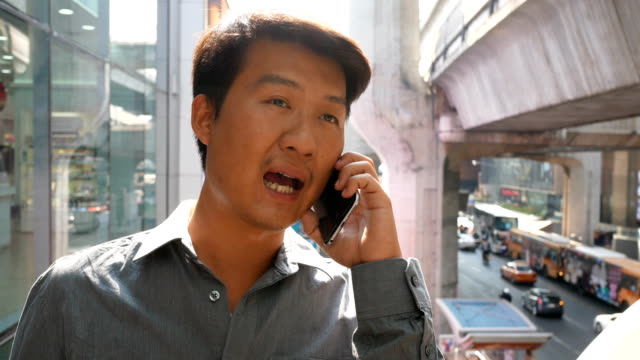 4k asian man talking on the phone - one mid adult man only stock videos & royalty-free footage
